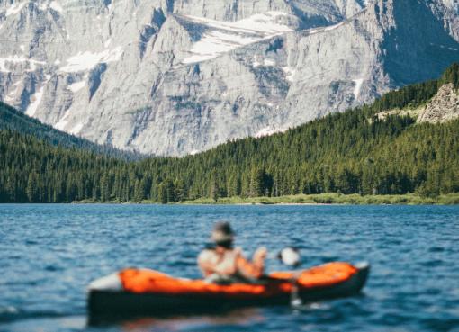 Рибар в надуваем каяк на фона на скалисти планини и иглолистна горичка