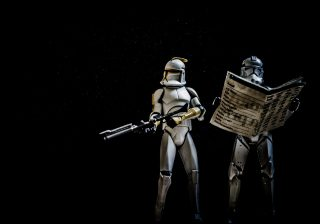 Clone Troopers on a black background - one of them is reading a newspaper and the other is holding a blaster