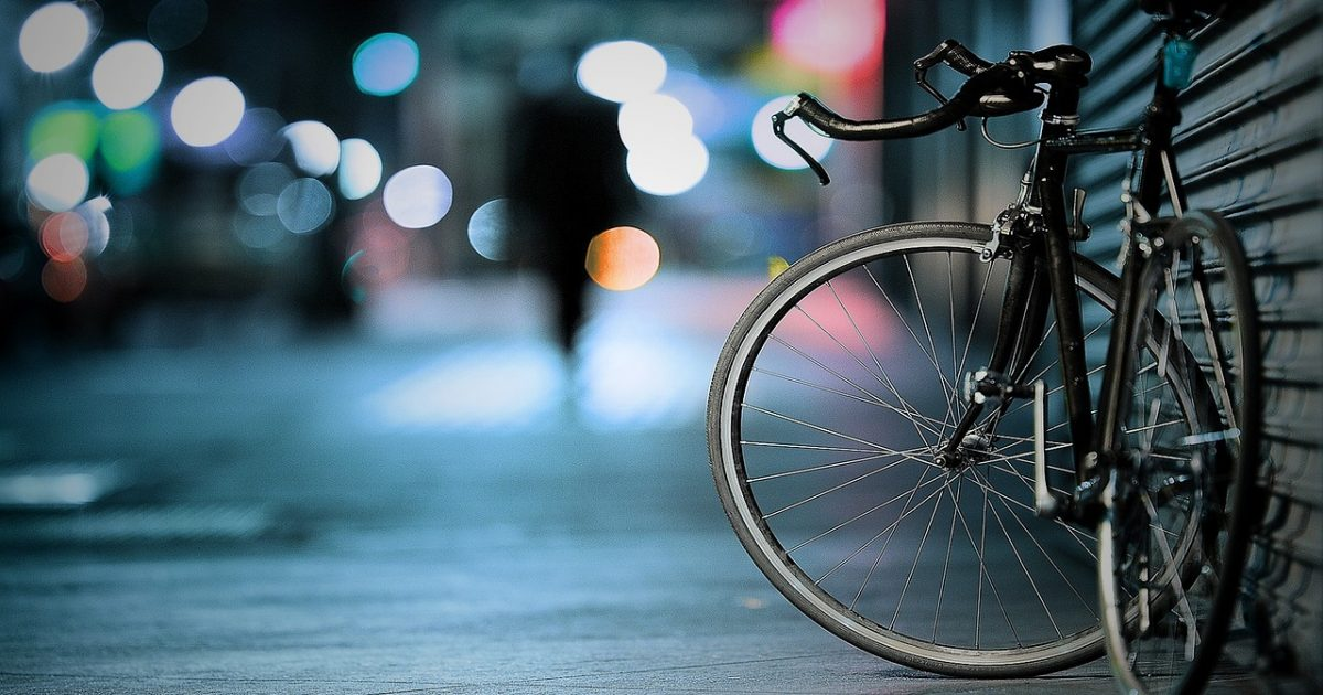 A bicycle propped next to a garage doot with a blurred person comming towards it
