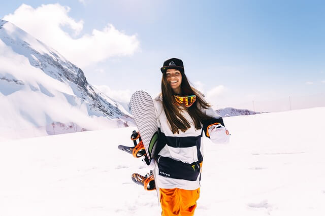 Усмихната жена с дълга коса, носеща бял сноуборд на фона на заснежен хълм