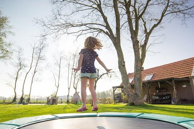 Момиче, което скача на батут в двора