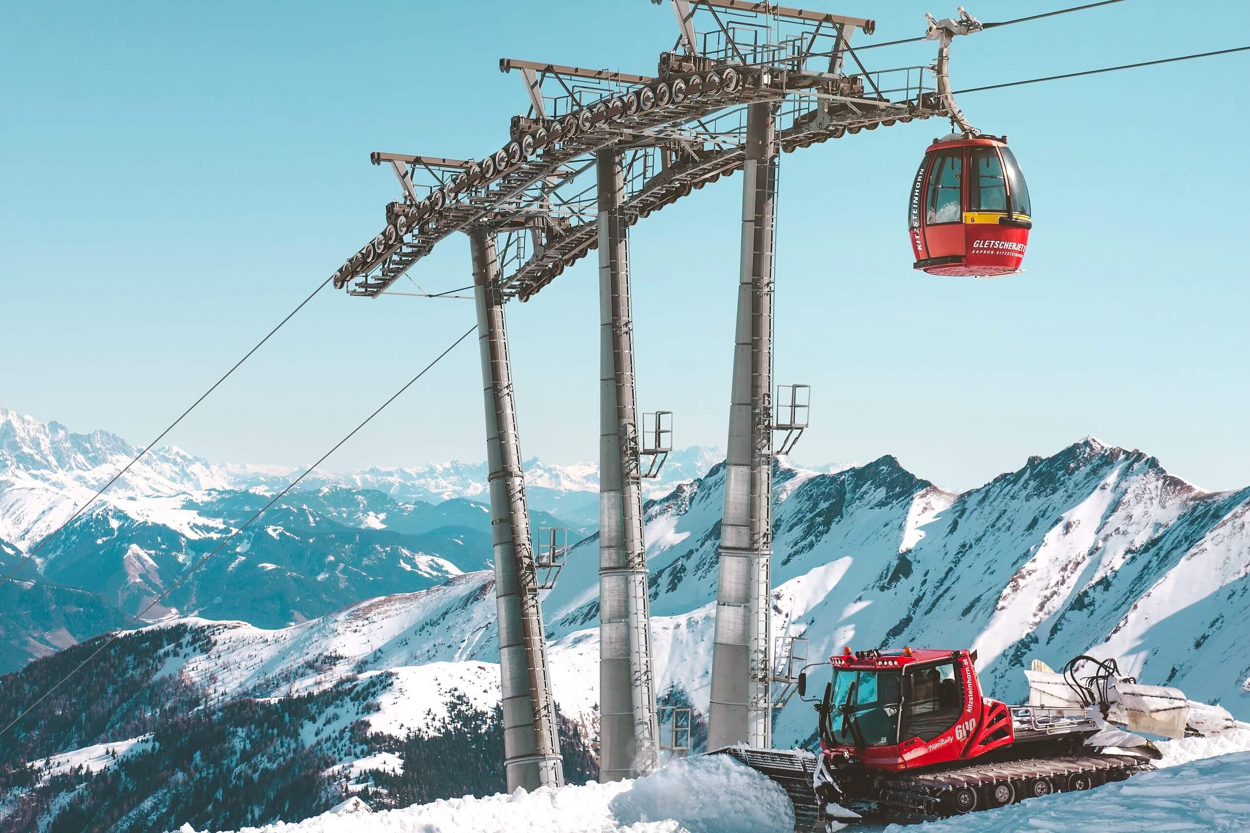 Снимка на лифт и снегорин на фона на заснежени върхове