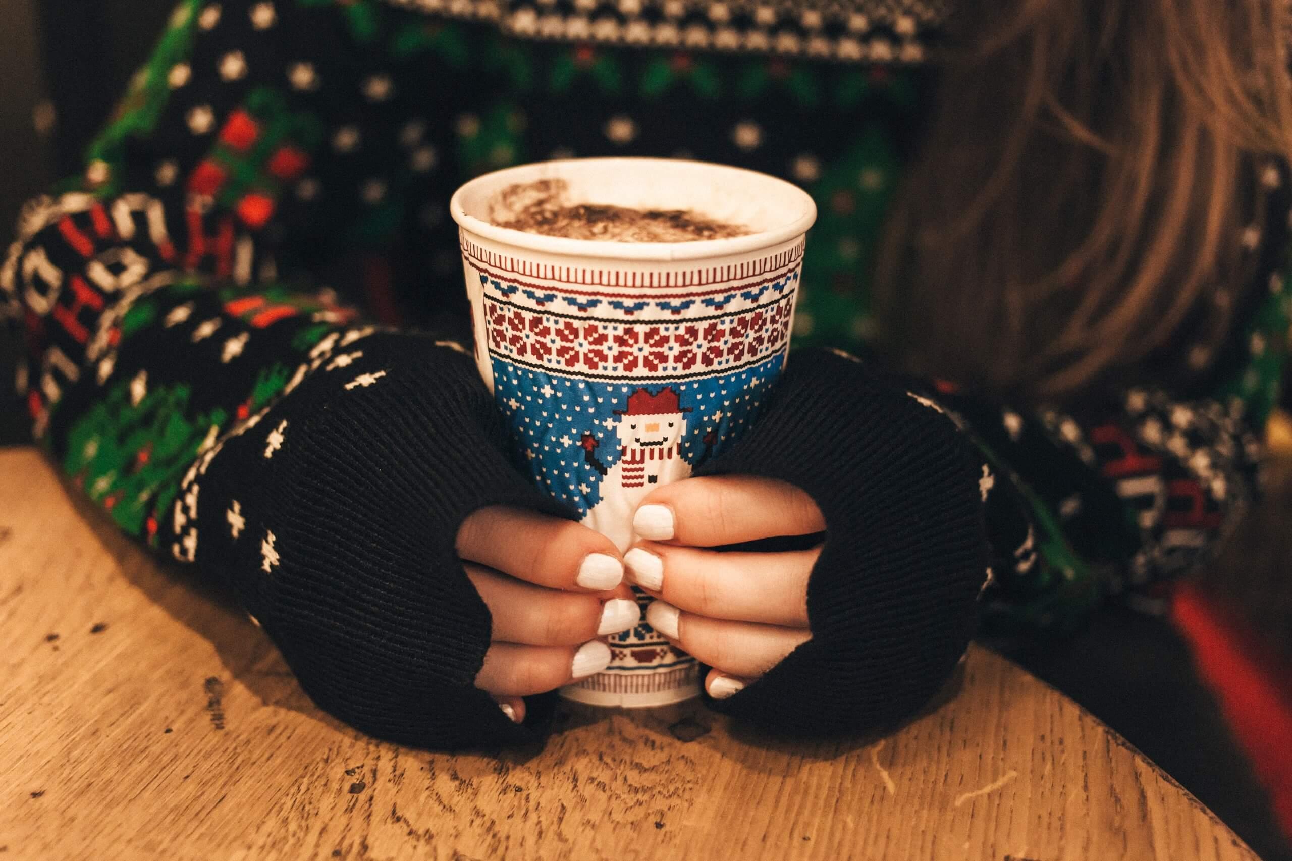 Снимка на коледна чаша със снежен човек, обхваната от женски ръце