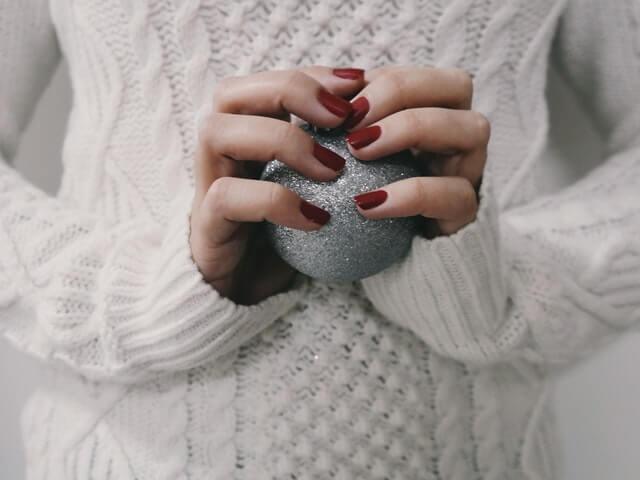 Жена с бял коледен пуловер държи сребриста топка за елха