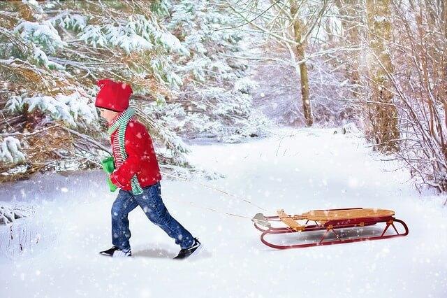 Дете с червено яке и шапка дърпа шейна по снега