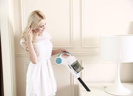 Жена в бяла рокля, която използва малка прахосмукачка
