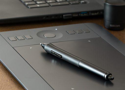 Графичен таблет Wacom с писалка върху активната плою и лаптоп във бекграунда
