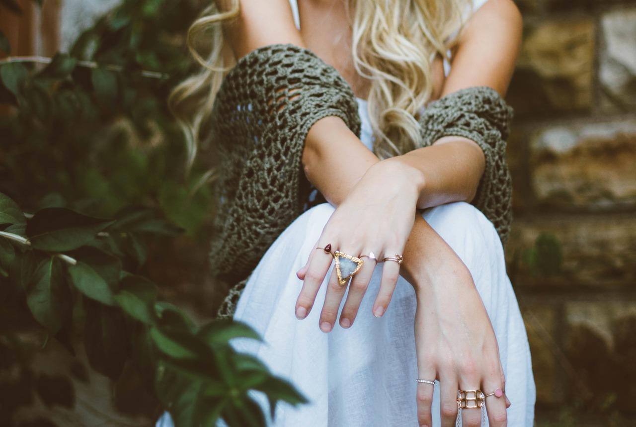 Жена в бяла рокля с красиви пръстени на двете ръце