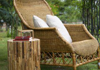 Градински фотьойл от естествен ратан с две бели възглавнички заснет в градина