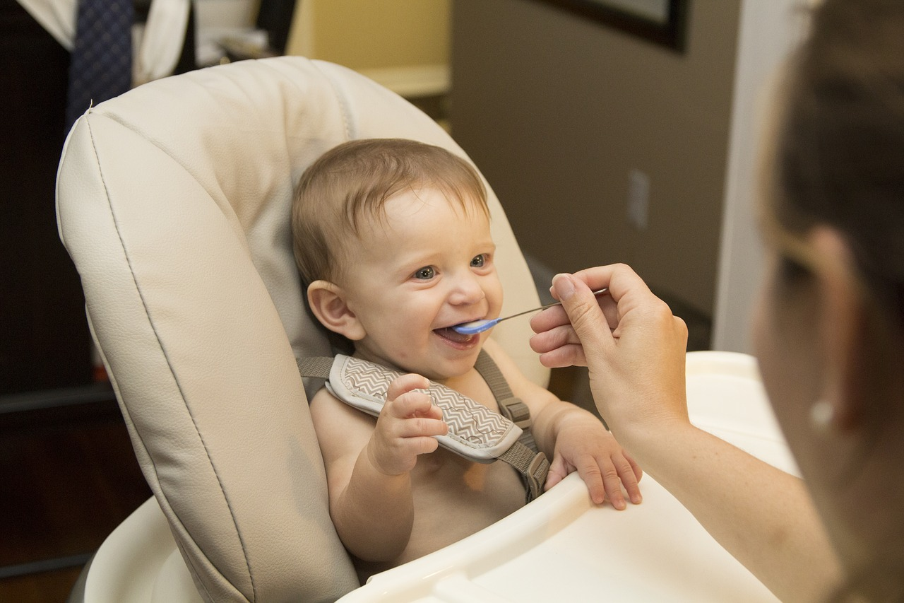 Майка храни бебе с лигавник, седнало на детско столче
