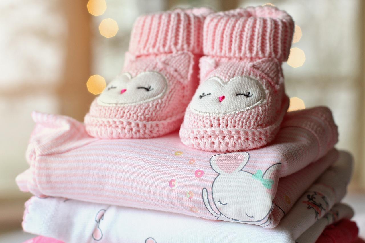 Розови бебешки ританки върху сгънати бебешки дрешки