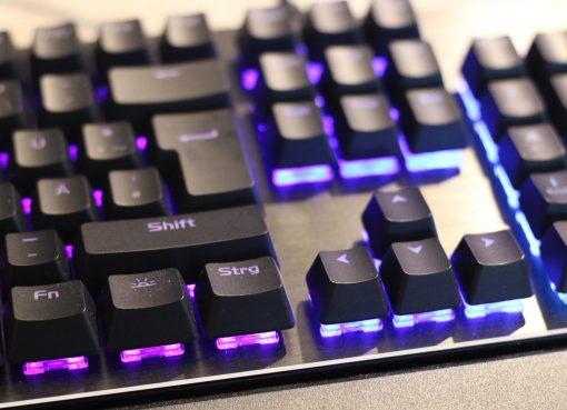 Снимка на геймърска клавиатура с лилава подсветка
