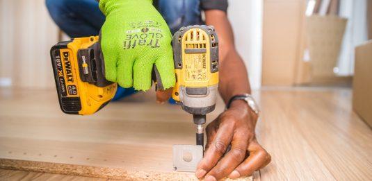 Човек, който завива метален елемент на дървена плоскост с жълт винтоверт DeWalt