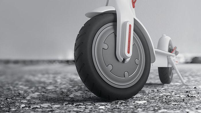 Близък план на предната гума на бяла електрическа тротинетка Xiaomi