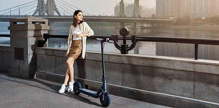 Жена позираща до електрическа тротинетка Xiaomi подпряна на мост