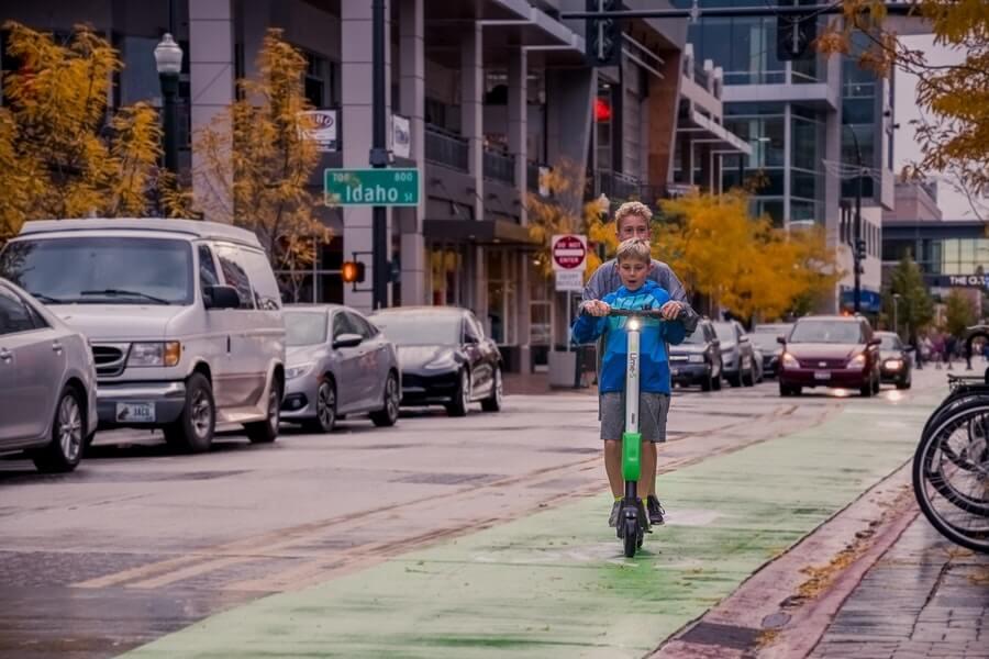 Две момчета, каращи електрическа тротинетка на зелена велоа алея в града.