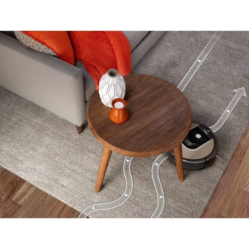 Roomba 966, която се движи под малка кръгла масичка за кафе и почиства сив килим