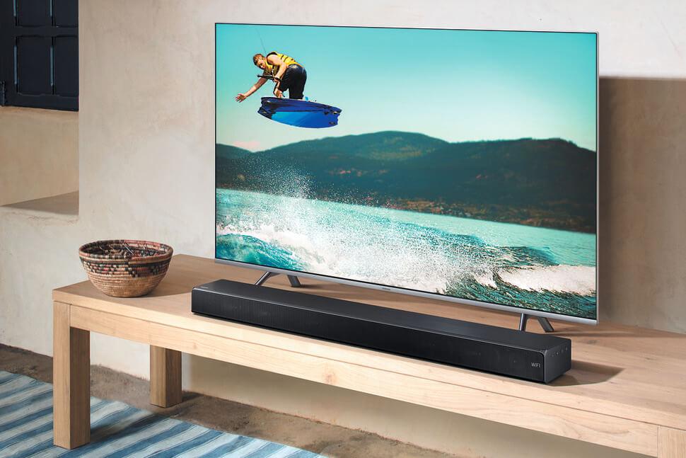 саундбар система на Samsung поставена на дървена масичка за телевизор с пуснат телевизор