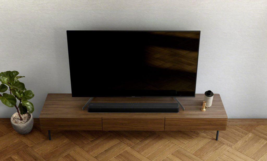 Саундбар HT-X8500 на масичка за телевизор с голям телевизор Sony Bravia