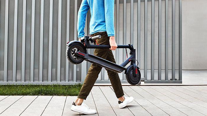 Кадър на мъж, който носи сгъната електрическа тротинетка Xiaomi