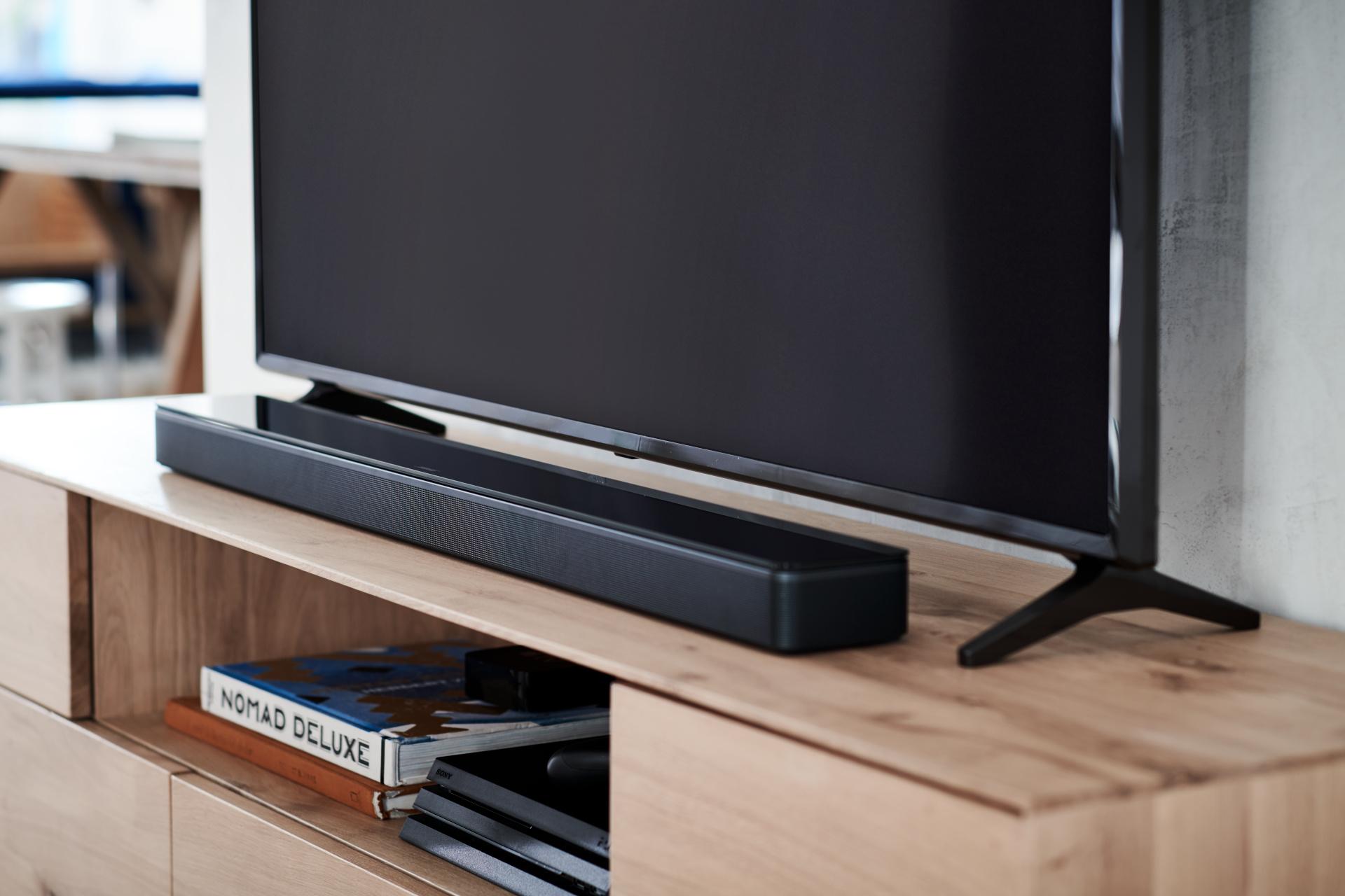 Bose саундбар система и smart телевизор, поставени на масичка за телевизор
