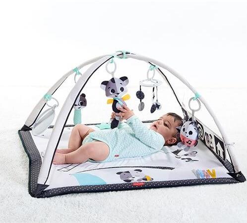 Бебе легнало по гръб в активна гимнастика, стискащо висяща играчка