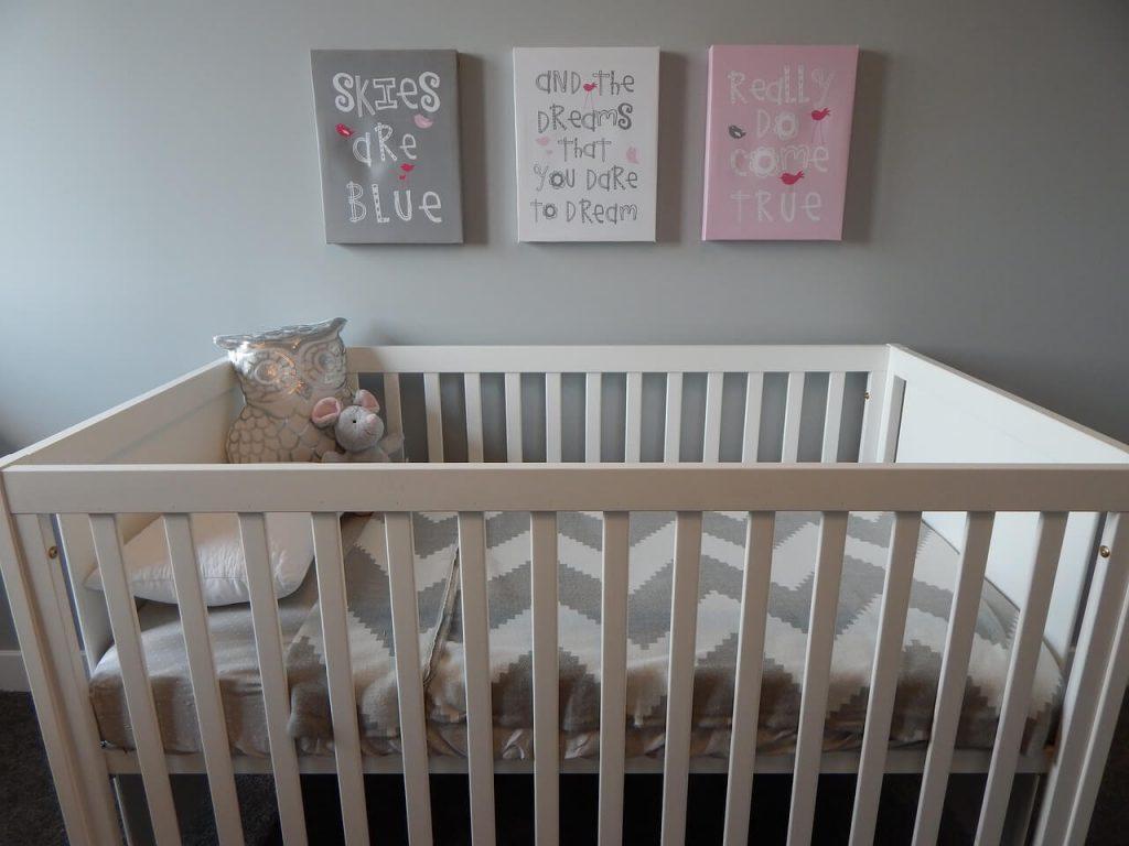 Бебешка кошара с чаршаф на вълнички и три картини с цитати на стената над кошарата