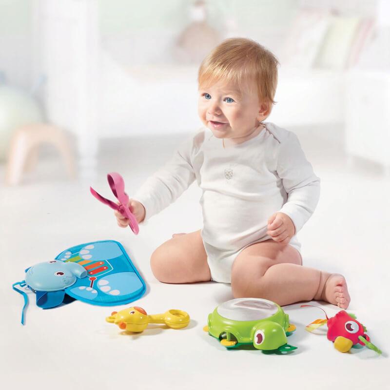 Русо бебе, което играе на пода с играчките от активна гимнастика