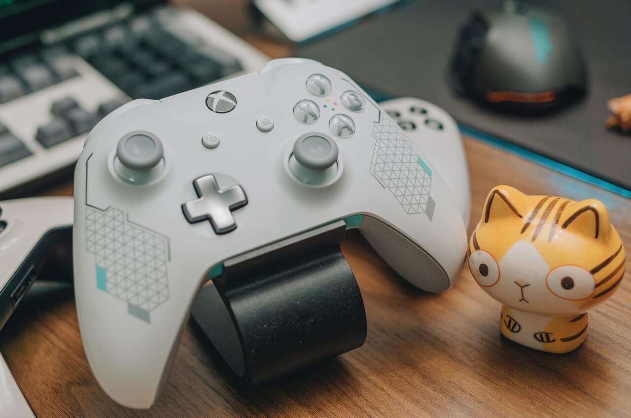 Бял Xbox One контролер в зареждаща станция с клавиатура и мишка на заден фон