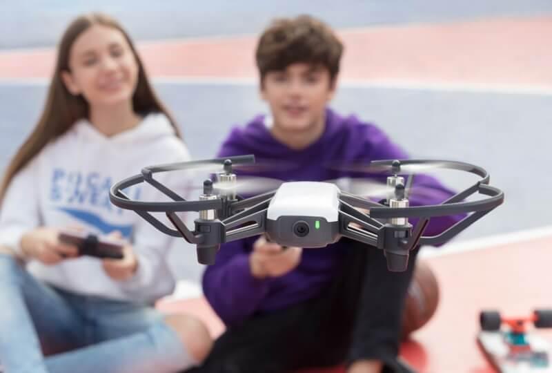 Две деца - момиче и момче, управляват дрон с камера за деца DJI Tello