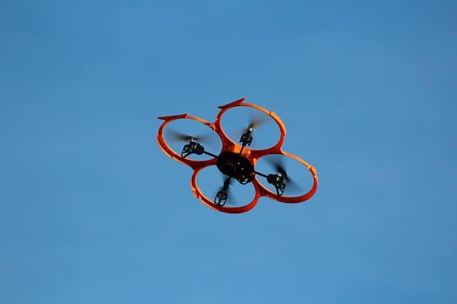 Дрон за деца с цели предпазители на витлата в полет на фона на синьо небе