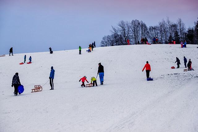 Заснежен хълм с деца и възрастни, които дърпат и се пързалят с шейни