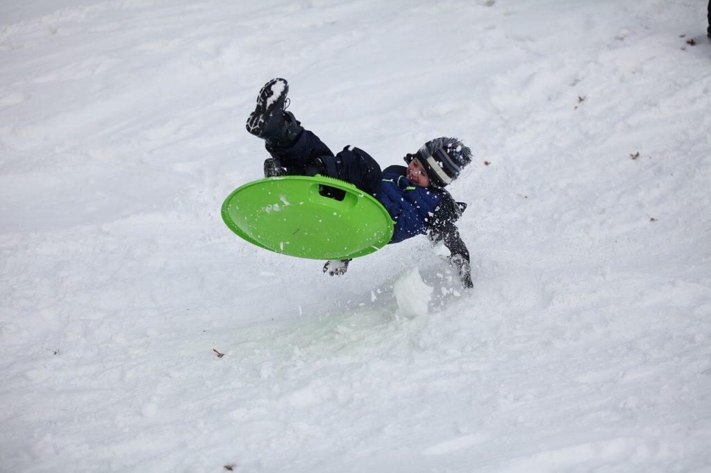 Дете, което се спуска по заснежен хълм със зелен слайдер